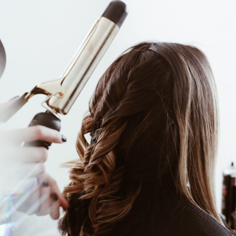 person holding gray hair curler